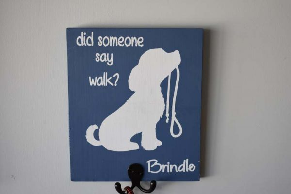 Wood sign with a dog outline that says did someone say walk