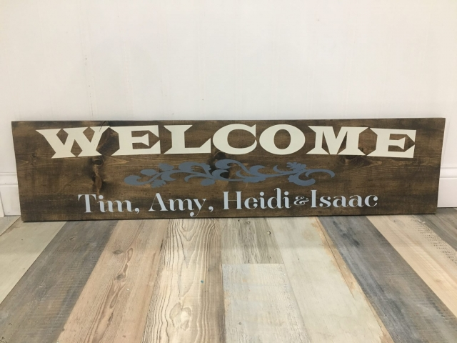 welcome sign with names on wooden sign