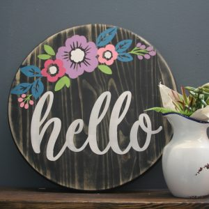 wood sign with floral print that says hello