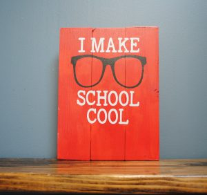 "Red sign with black glasses that says ""I make school cool"""