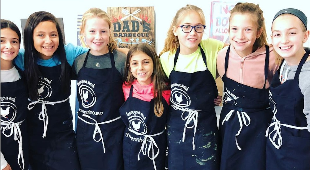 Kids wearing aprons smiling at the camera