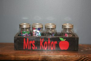 Black and red planter box with teacher's name and an apple