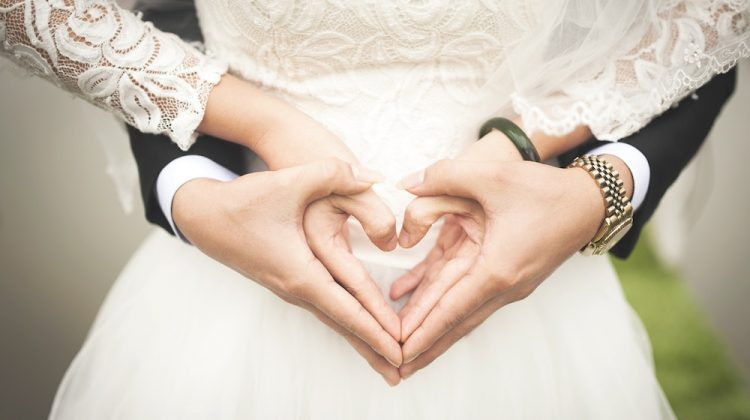 Bride and groom holding hands and making a heart with their thumbs and fingers
