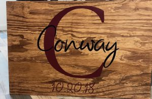 Wooden sign with last name and monogram for wedding guests to sign