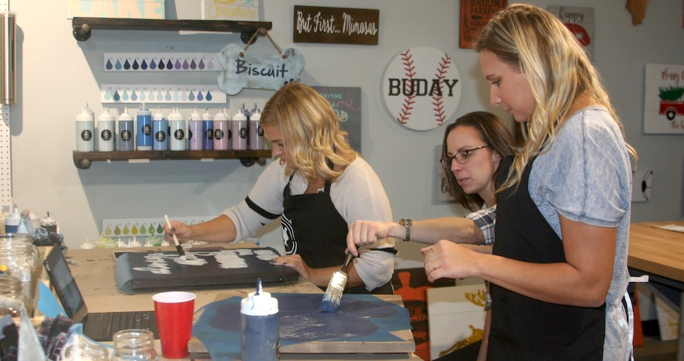 Women painting custom wood signs at a workshop
