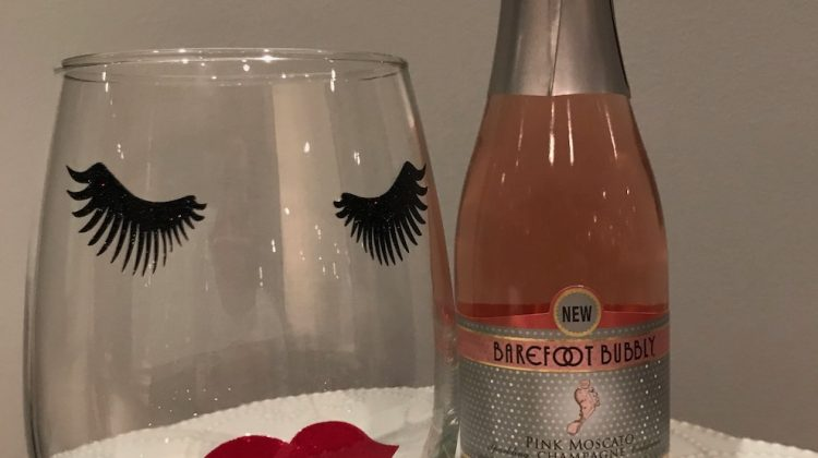 Wine glass with painted eyelashes and lips next to a small wine bottle