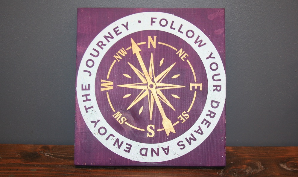 purple wood sign with compass that says follow your dreams and enjoy the journey