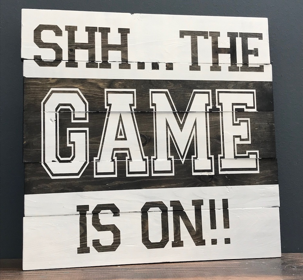 Black and white wood sign that says SHHHH the game is on