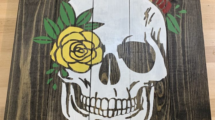 wood sign with skull and flowers