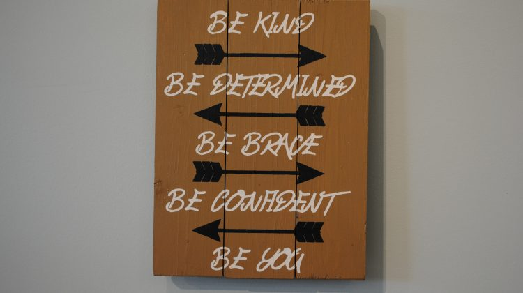 wood sign that says be kind, be determined, be brave, be confident, be you