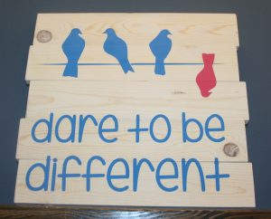 wood sign that says dare to be different