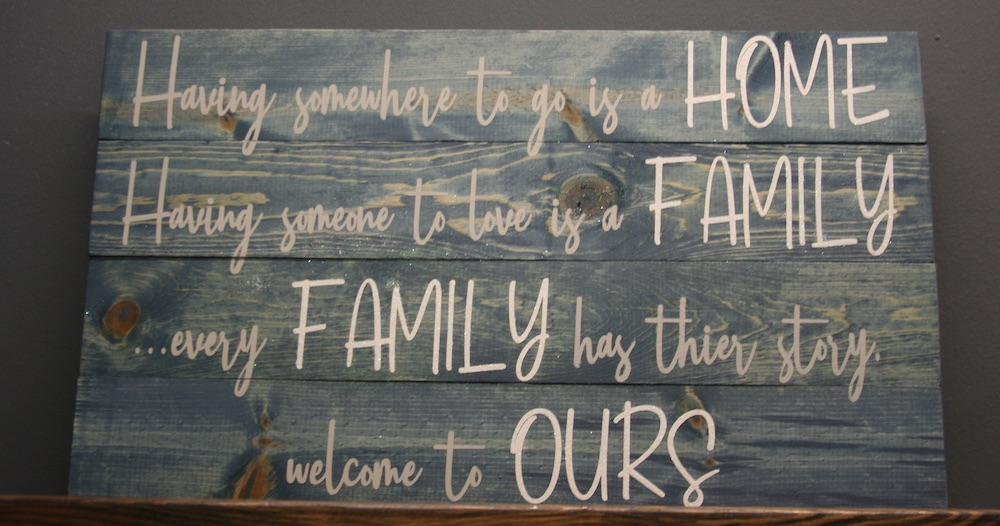 Blue wood sign with quote about home and family