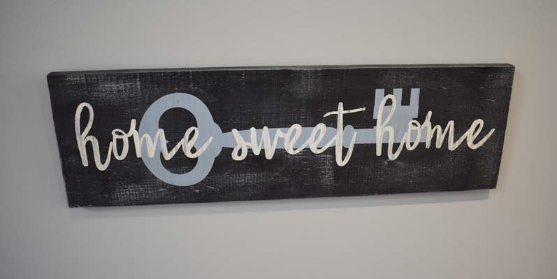 Wood sign with key image that says home sweet home