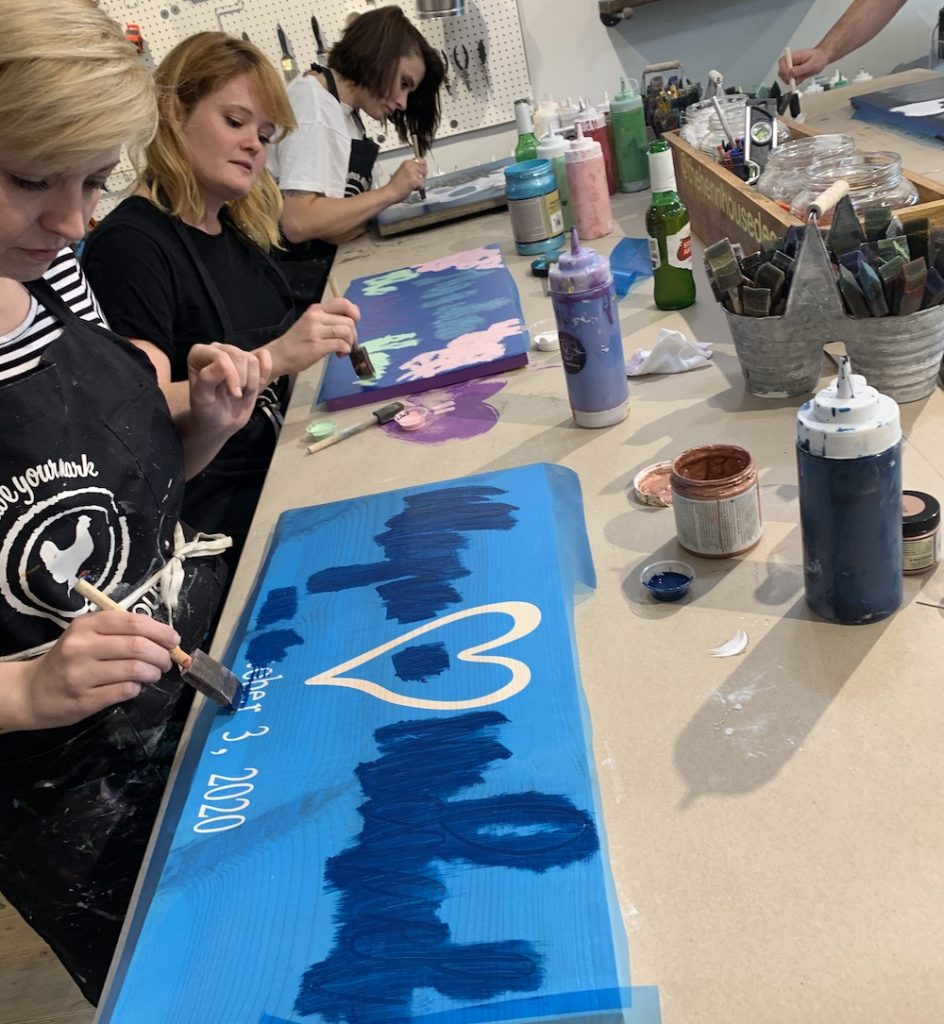 Three woman painting wood signs